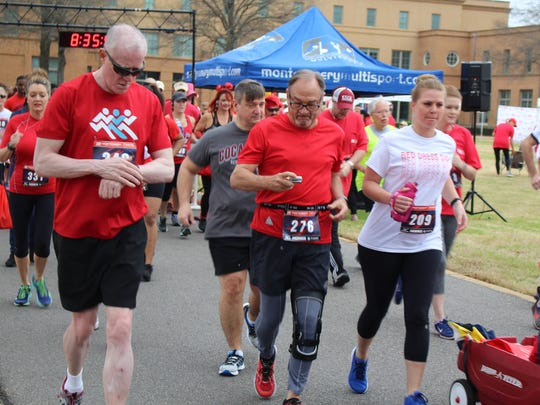 Runners check their times during Saturday's Red Dress Dash that attracted hundreds of athletes. Alvin Benn/Special to the Advertiser