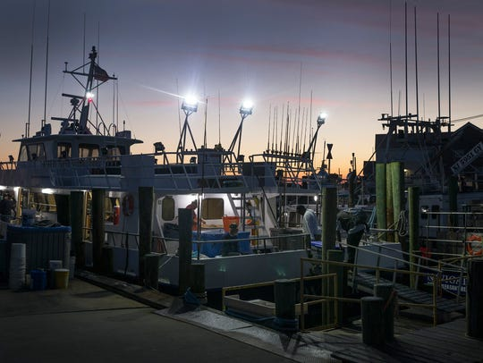Passengers slowly load a day fishing boat to head out