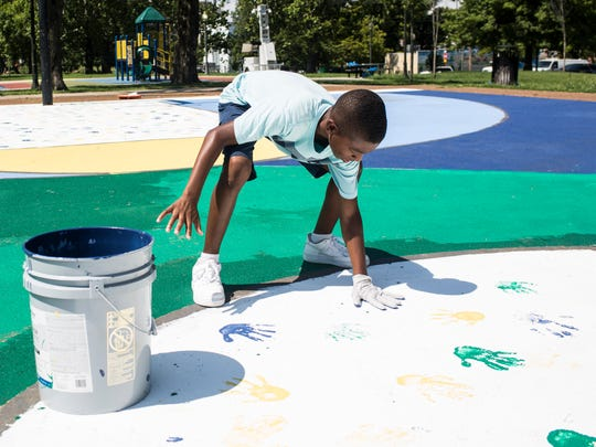 July 11, 2018 - Keshun Partee, 12, presses his painted