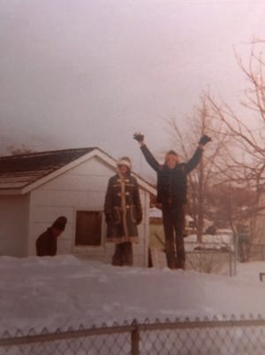 Jeff Gibson (right) and his sister Alisa Gibson Needles (left) stand atop a snow drift from the 1978 blizzard. The drift grew higher than the fence in their yard.