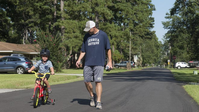 Wes Eminger walks along Symons Street as his son, Wyatt, 4, rides his bike on Tuesday. Eminger lives in the Gleason Heights neighborhood in Pooler, where a group of neighbor have been fighting a large development called the Pooler Promenade since April 2019. The neighbors argue that the development would bring more traffic to Symons Street which would make the streets in their neighborhood less safe.