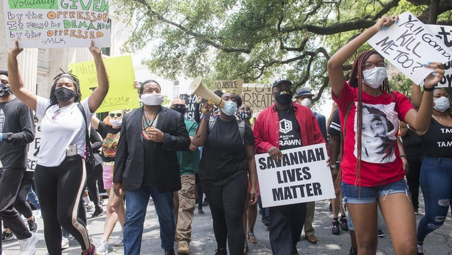 A crowd of protesters march from Johnson Square to Savannah city hall on Sunday.