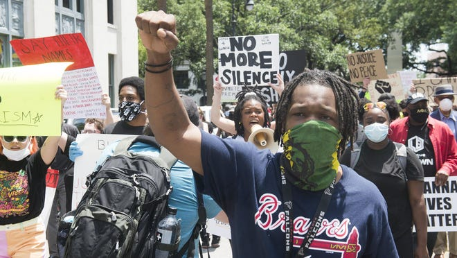 A crowd of protesters march on Savannah city hall on Sunday.