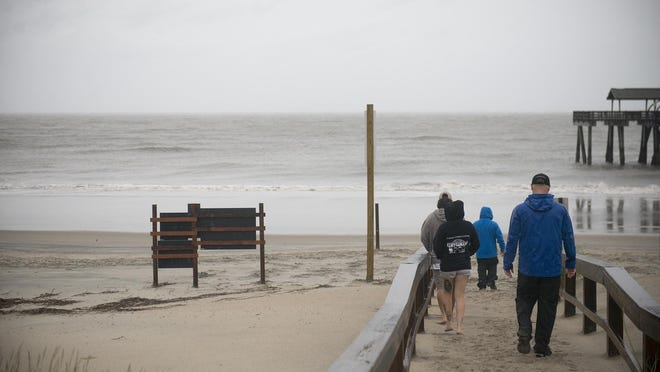 People walk onto the beach at Tybee Island.