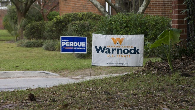 Campaign signs for Georgia Senate Runoff Candidates David Perdue and Raphael Warnock stand opposite one another outside houses on Paulsen Avenue.