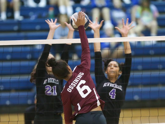 Ossining's Mychael Vernon (6) hits a kill shot as New Rochelle's (21) and Isabella Clayton (4) block during the Section 1 Class AA volleyball finals at Pace University in Pleasantville on Sunday, November 5, 2017.