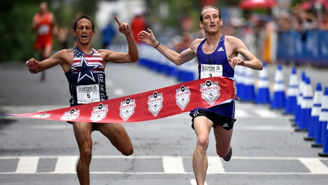 Winner of the men's AJC Peachtree Road Race Scott Overall, right, breaks away from Ben Payne who finished second Saturday, July 4, 2015, in Atlanta.