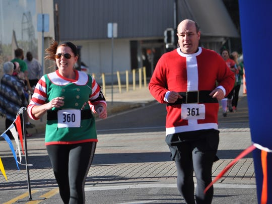 Katherine and Jeff Goins cross the finish line together after completing the Alex Winter Fete Ugly Sweater 5K.