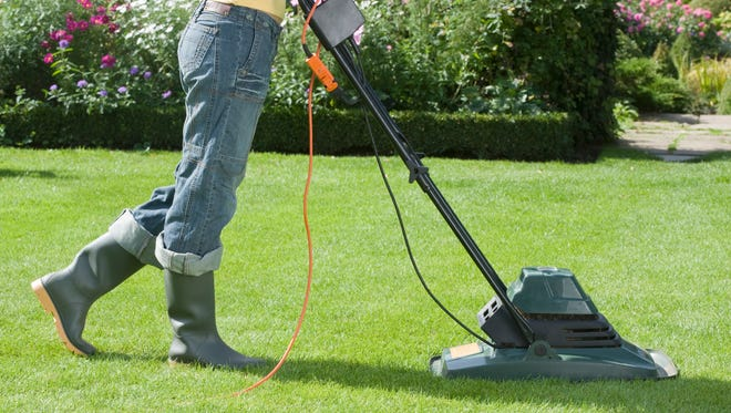 Woman mowing with electric mower.