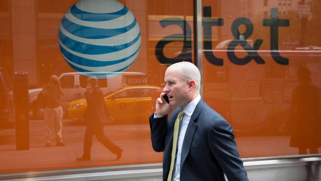 In this Tuesday, June 23, 2015, photo, a man using a mobile phone walks past an AT&T store, in New York. AT&T Inc. reports earnings, Tuesday, July 25, 2017.