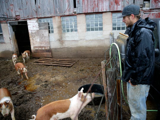 Justin Duell fills a container of water for his pigs