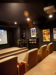 The walls of the home theater are covered in dark green