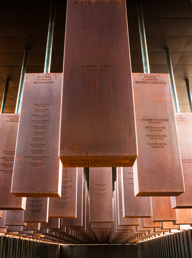 Walking through the memorial, the floor slopes down and the memorial columns rise overhead.