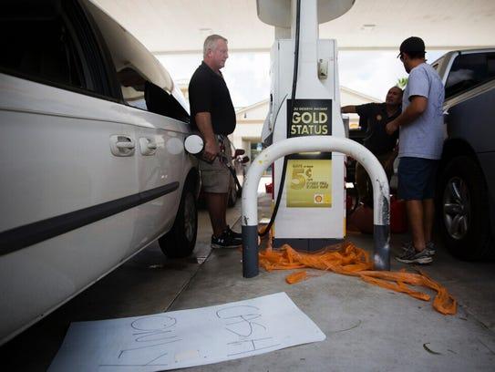 Derek Delgado, left, pumps gas into his car at the
