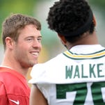 Green Bay Packers quarterback Scott Tolzien (16) smiles as he talks with Josh Walker (79) during minicamp at Clarke Hinkle Field June 18, 2015.