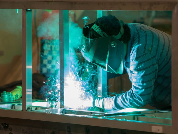 Julio Romero uses a welder on a sign at VoxLumen in the former Diamond Foods building on Exit Five Parkway, Fishers, March 17, 2014.
