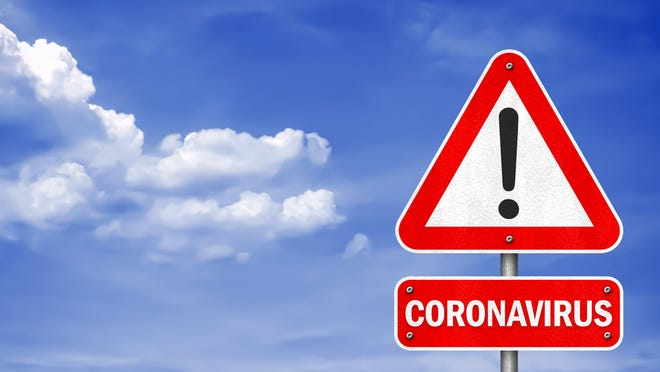 A red warning sign for coronavirus set against a blue sky.