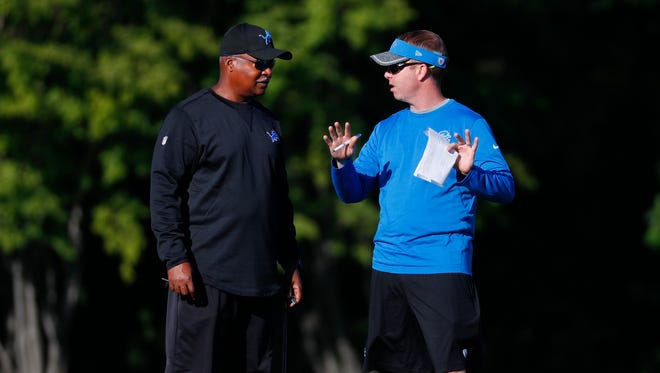 Lions head coach Jim Caldwell, left, talks with GM Bob Quinn during a practice in Allen Park on Aug. 8, 2016.