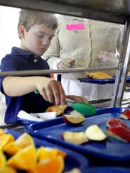 Student Jack Cochran, 9, adds fruit to his lunch tray