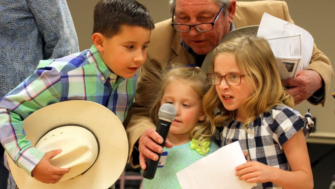 Bobby Smrkovsky, president for the Luna County Old-Timers' Association, orchestrates his grandchildren in leading reunion guests in the Pledge of Allegiance during opening ceremonies of the 105th annual reunion on Saturday at the Mimbres Valley Special Events Center.
