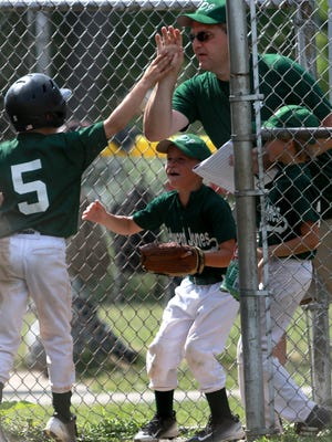 Zach Gainer is congratulated by teammates and his coach after scoring a run in the Shrine Tournament quarterfinals Saturday.