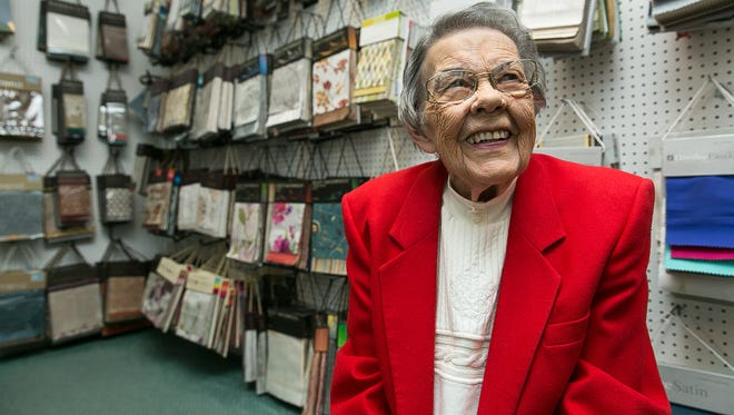 Spring Crest Custom Draperies owner Donna Kosnick, 84, smiles while sitting at the store on Monday with samples of material on display in the background. On Jan 15, 2016 the family-owned store will be celebrating its 40th anniversary.
