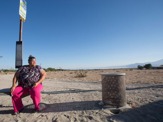Blanca Barraza looks to see if a bus is coming in North