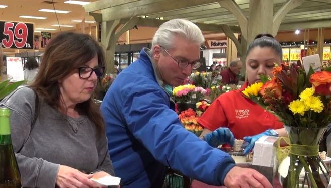 Terry Lally of Webster, center, samples prepared hors d'oeuvres at a seminar on hosting a grazing party at the Holt Road Wegmans store.