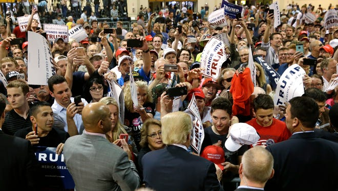 Supporters take photographs and seek autographs from Republican presidential candidate Donald Trump, lower center, at a rally in Eugene, Ore., Friday, May 6, 2016. (AP Photo/Ted S. Warren)