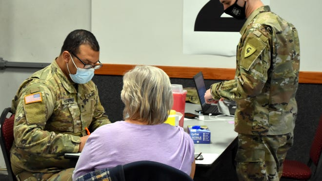Michigan National Guard members prepare to give a COVID-19 shot at the Dearth Center Thursday during a small clinic.