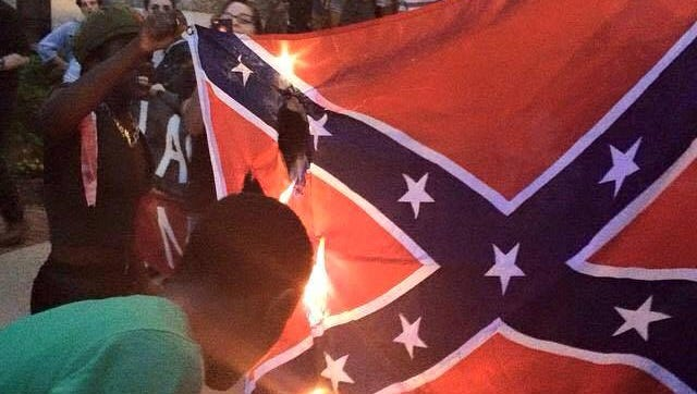 BLACC's lead organizer Regina Joseph (left) and Alex Gaskin (right) is seen burning the confederate flag outside Tallahassee's Capitol building. The photo has since gone viral, becoming a national symbol against white supremacy.