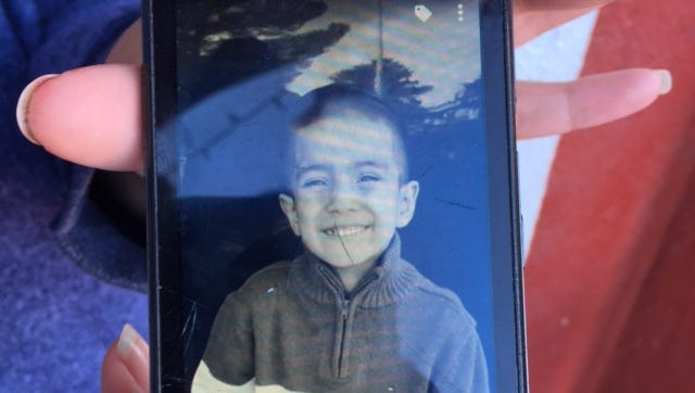 Nathan Valdez's relative, Olga Enriquez, shows a photo of him on her smartphone. Nathan died after being struck by a car on Feb. 10, 2016.