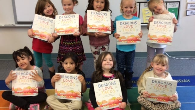 Preschool students at Washington Elementary hold up their new books given to them by the Assistance League of Southern Utah.