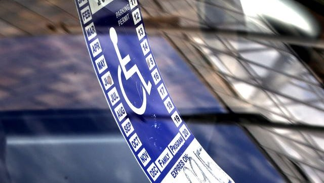 A parking tag for people with disabilities hangs from the rearview mirror of a car at a metered parking spot.