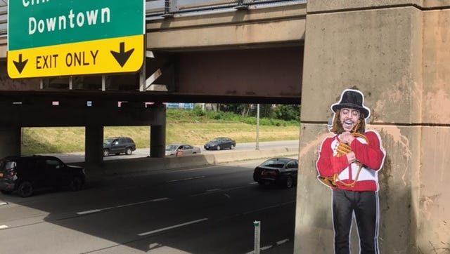 Dellarious' latest caper: Chuck Mangione looks down on Interstate 490 in honor of Jazz Fest. Someone defaced the piece with paint, but Dellaria put up a second version.