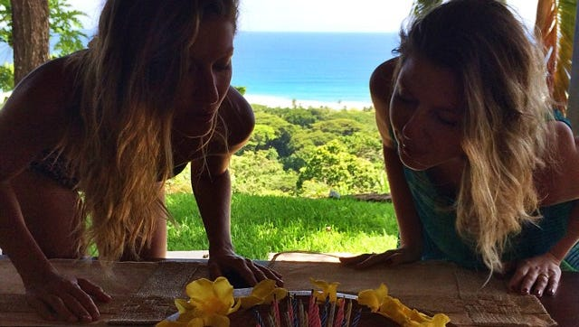 Gisele Bundchen shared a photo of herself blowing out candles on a cake with twin sister Patricia.