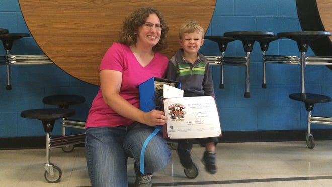 Kerri and Nathan Van Asten accept a certificate in honor of the family's donation of $250 worth of Box Tops for Education to Appleton Public Montessori School.