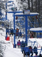 Skiers and snowboarders ride the chairlift at Hidden