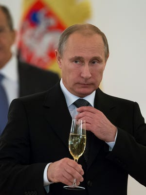 In this file photo taken Wednesday, Nov. 19, 2014, Russian President Vladimir Putin prepare to toast with ambassadors in the Alexander Hall after a ceremony of presentation of credentials by foreign ambassadors in the Grand Kremlin Palace in Moscow, Russia.