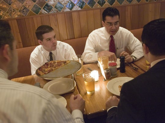 Marco Lopez (right) eats dinner in Phoenix with Jeff Peterson (left) and others in November 2005.