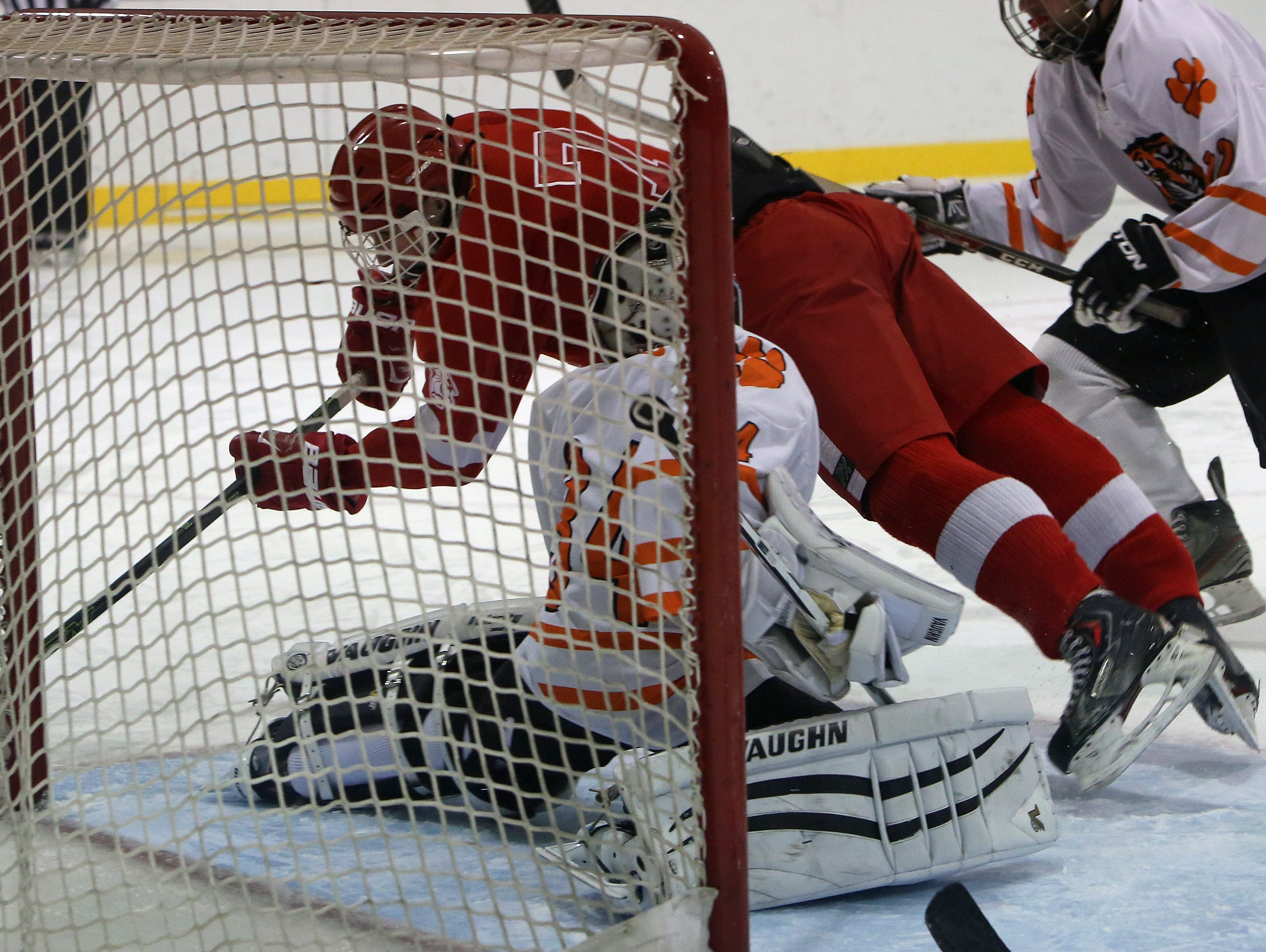North Rockland's Bryan Jensen (7) dives over White Plains' goalie Justin Schulz (34) as he tries to get a shot by him during hockey action at Ebersole Ice Rink in White Plains Jan. 7, 2016. The game ended in a 4-4 tie.