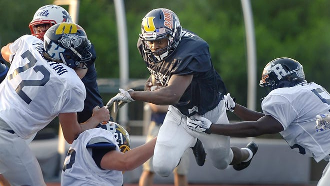 Spencerport's Xavier Eaddy, center, dives over the pile during the 33rd Annual Eddie Meath All-Star Game played at Eastridge High School on July 11, 2015.