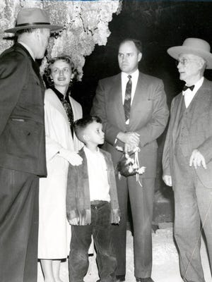03/23/1958 Saturday was a record-breaking day at Carlsbad Caverns National Park, N.M. Mrs. Ward Brown of Waukesha, Wis., was ticked off as Visitor No. 8 million. Photo shows Park Supt. Taylor Haskins, left, explaining a portion of the Caverns to Mrs. Brown, second from left. Her husband, Dr. Ward Brown, is at her side along with son, Buster, 5. J.N. Nevenger, 95, a member of the first organized tour in 1922, is at right.