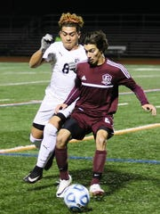 Dover senior Sebastian Montoya and Newton midfielder Kevin Ayoso battle for the ball during the first half of a NJSIAA Group II semifinal at Ridge High School.