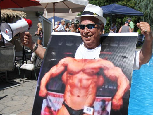 ASB 0810 Howell Family Picnic Asbury  Mike Bellisano, who celebrated his 80th birthday in May, jokes around using a poster board of a muscleman during the Bellisano 50th family reunion in Howell, Sunday, August 10, 2014.  Mary Frank/Staff Photographer