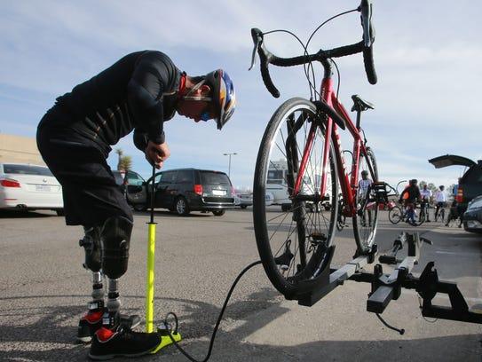 Carlos Gutiérrez fills a bicycle tire with air prior