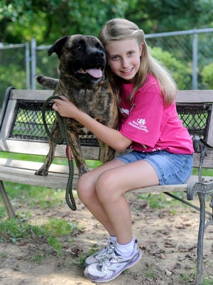 Allison Lutz, 10, poses for a photo with one of the dogs available for adoption at the Ross County Humane Society on Wednesday. Allison was asking for donations to the shelter in lieu of birthday gifts for her tenth birthday this year.