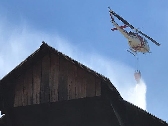 A helicopter douses a fire that broke out July 16,