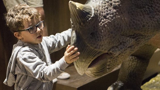 Kids play with animatronic dinosaurs at Pangaea Land of the Dinosaurs on Friday, Dec. 8, 2017, in Scottsdale.