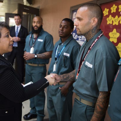 Attorney General Loretta Lynch shakes hands Friday with Derrick Cash during a visit to Talladega Federal Correctional Institution in Alabama to highlight policies that aim to reduce barriers for formerly incarcerated individuals.